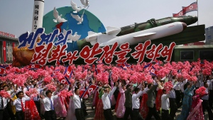 North Koreans wave national flags and artificial flowers as they march next to a float with models of different missiles across Kim Il Sung Square during a military parade to celebrate the 105th birth anniversary of Kim Il Sung in Pyongyang, North Korea, Saturday, April 15, 2017. (AP / Wong Maye-E)