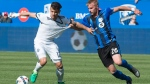 Montreal Impact defender Kyle Fisher hangs on to Vancouver Whitecaps forward Fredy Montero as they battle for the ball during second half MLS action Saturday, April 29, 2017 in Montreal. THE CANADIAN PRESS/Paul Chiasson
