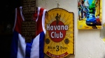 In this Friday, April 28, 2017 photo, several gift items including a painting with the Cuban Havana Club rum logo hang at a souvenir shop in Havana, Cuba. (AP Photo/Ramon Espinosa)