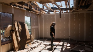 Stephanie Quezada looks at the damage to the second floor of her father's church, Primera Iglesia Bautista, in Canton, Texas, Sunday, April 30, 2017. Severe storms including tornadoes swept through several small towns in East Texas, killing several and leaving a trail of overturned vehicles, mangled trees and damaged homes, authorities said Sunday. (Sarah A. Miller/Tyler Morning Telegraph via AP)