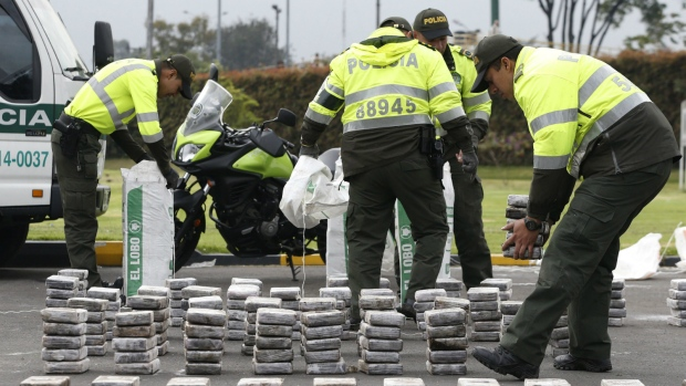 Police unpack bags of seized cocaine as they display it to the press at the police station in Bogota, Colombia on Thursday, Sept. 8, 2016. (AP / Fernando Vergara)