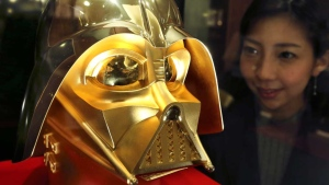 Tokyo gold jeweler Ginza Tanaka employee Momoko Marutani looks at the gold mask of Darth Vader at the jewelry shop in Tokyo, Monday, May 1, 2017. (AP Photo/Koji Sasahara)