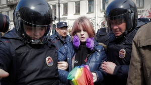 A gay rights activist holding a rainbow umbrella is detained by police during a rally marking May Day in downtown St. Petersburg, Russia, Monday, May 1, 2017. (Dmitri Lovetsky/AP)