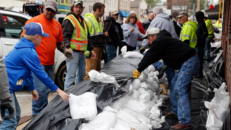 Volunteers place sandbags to protect buildings from potential floodwater Monday, May 1, 2017, in Eureka, Mo. (AP / Jeff Roberson)