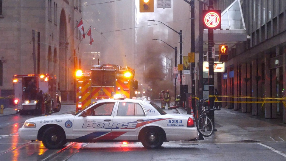 Police are clearing a busy intersection in downtown Toronto as smoke pours from a grate and loud blasts are heard on Monday, May 1, 2017. An officer at the scene was telling people to move away from the area, near King and Yonge street. (THE CANADIAN PRESS/Joe O'Connal)
