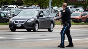 An Omaha police officer points his rifle in the direction of a vehicle driven by an inmate who escaped from the Pottawattamie County jail in Council Bluffs, Iowa, and carjacked a Nissan Sentra, Monday, May 1, 2017, in Omaha, Neb. The inmate was captured after crashing the stolen vehicle. (Chris Machian/The World-Herald via AP)