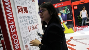 In this Thursday, April 28, 2016, photo, a woman visits a display booth for the Chinese internet portal 163.com promoting its news section, at the Global Mobile Internet Conference (GMIC) in Beijing. (Andy Wong/AP)