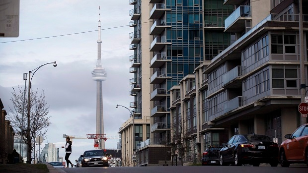 The CN Tower can be seen behind condo's in Toronto's Liberty Village community in Toronto, Ontario on Tuesday, April 25, 2017. (THE CANADIAN PRESS/Cole Burston)