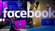 In this Tuesday, April 18, 2017, file photo, a conference worker passes a demo booth at Facebook's annual F8 developer conference, in San Jose, Calif. Facebook Inc. reports earnings, Wednesday, May 3, 2017. (AP Photo/Noah Berger, File)