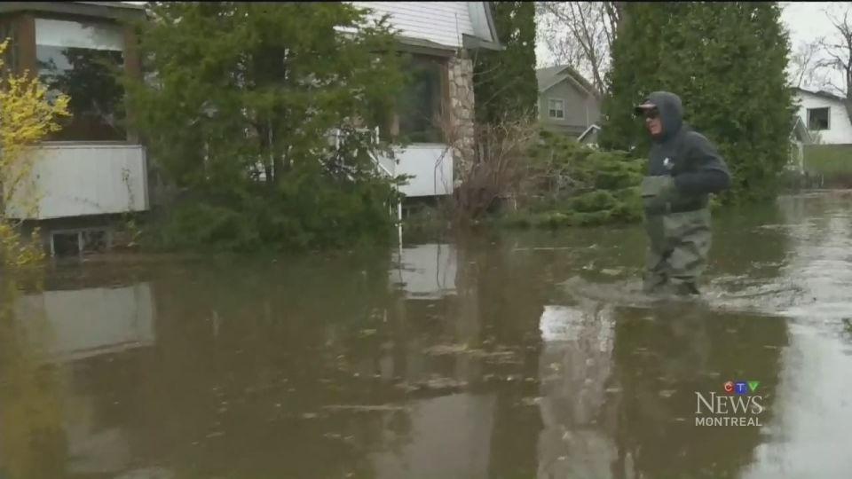 A man in hip waders walks through floodwaters near his Pierrefonds home on May 3, 2017