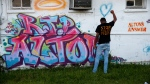 Damon Brumfield, a student at Southern University of Baton Rouge, poses while his friends take photos, in front of a mural honoring Alton Sterling, outside the Triple S Food Mart in Baton Rouge, La., Tuesday, May 2, 2017. (AP Photo/Gerald Herbert)