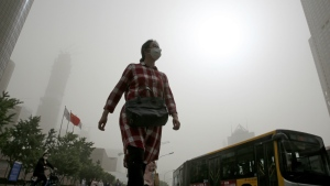 A woman wearing a face mask walks on a street as Beijing is hit by polluted air and sandstorm on Thursday, May 4, 2017. (AP / Andy Wong)