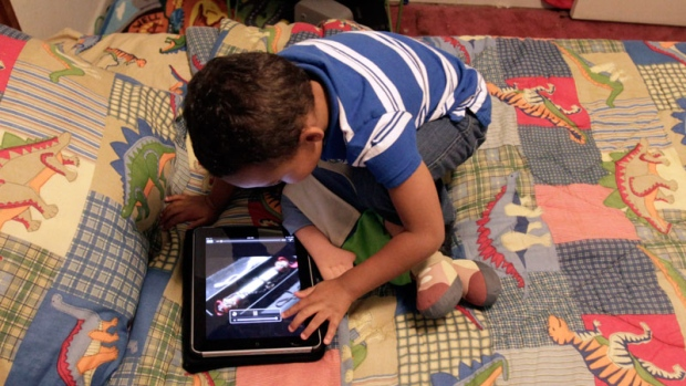 A preschooler plays with an iPad