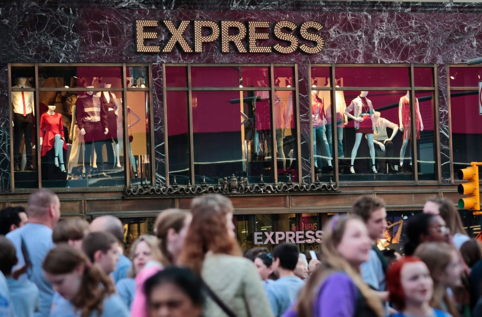 People walk by an Express store in New York's Times Square, Wednesday, March 9, 2016. (AP Photo/Bebeto Matthews)