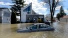 A car sits abandoned in floodwaters on Rue Saint-Louis in Gatineau, after flooding caused by significant rainfall, on Wednesday, May 3, 2017. (Justin Tang/The Canadian Press)