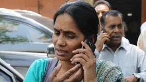 Asha Devi and Badri Singh, mother and father respectively, of the victim of the fatal 2012 gang rape on a moving bus, speak on their mobile phones as they arrive at the Supreme Court complex in New Delhi, India, Friday, May 5, 2017. (AP / Altaf Qadri)
