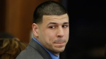 In this April 14, 2017, file pool photo, former New England Patriots tight end Aaron Hernandez turns to look in the direction of the jury as he reacts to his double murder acquittal after the sixth day of jury deliberations at Suffolk Superior Court in Boston. (AP Photo/Stephan Savoia, Pool)
