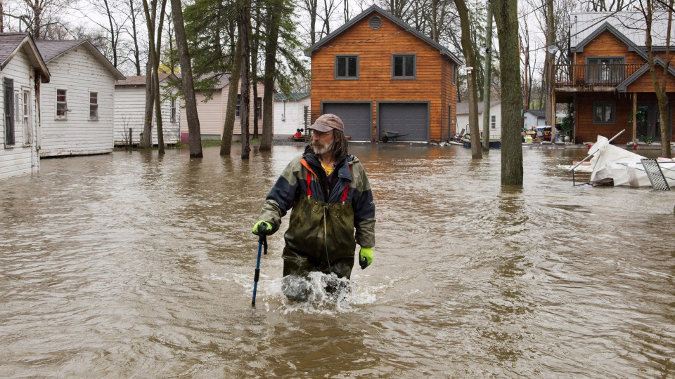 A resident walks through the flooded streets in the Ile-Mercier district of Ile-Bizard, Que. Friday, May 5,2017. (Ryan Remiorz / THE CANADIAN PRESS)