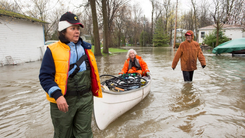 Residents use a canoe as they bring supplies through flooded streets of the Ile-Mercier district of Ile-Bizard, Que. Friday, May 5,2017.  (Ryan Remiorz / THE CANADIAN PRESS)
