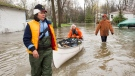 In this file photo, residents use a canoe as they bring supplies through flooded streets of the Ile-Mercier district of Ile-Bizard, Que. Friday, May 5,2017 . (THE CANADIAN PRESS / Ryan Remiorz)