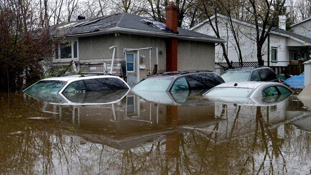 Several cars left in a driveway are filled with water in Gatineau, Que., as rising river levels and heavy rains continue to cause flooding, on Saturday, May 6, 2017. THE CANADIAN PRESS/Justin Tang