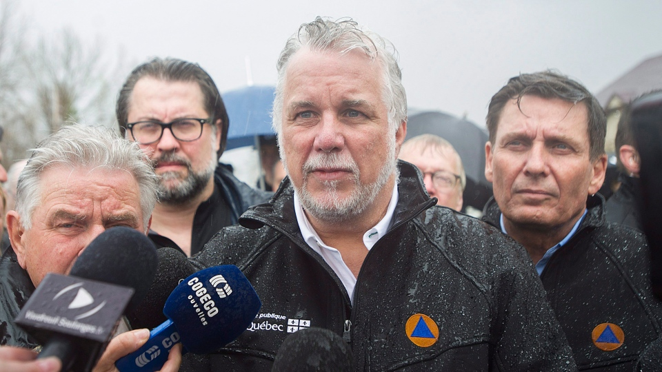 Quebec Premier Philippe Couillard speaks to reporters during a visit to a home surrounded by flood waters in the town of Rigaud, west of Montreal, Saturday, May 6, 2017, following flooding in the region. (THE CANADIAN PRESS / Graham Hughes)