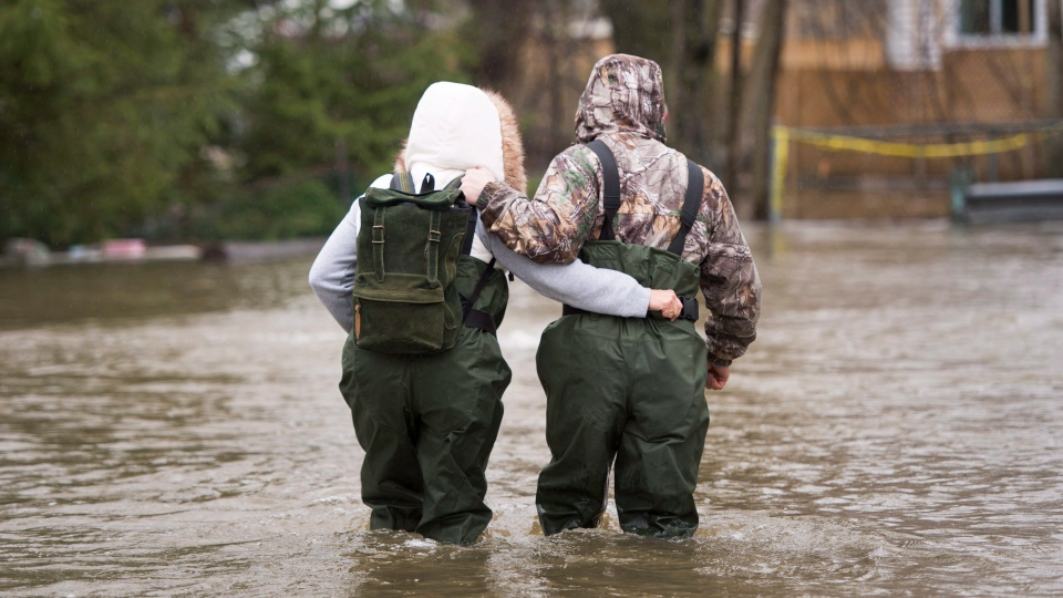 A couple walks through the flooded streets in the Ile-Mercier district of Ile-Bizard, Que. Friday, May 5,2017. Forecasts are calling for several more days of rain. (THE CANADIAN PRESS / Ryan Remiorz)