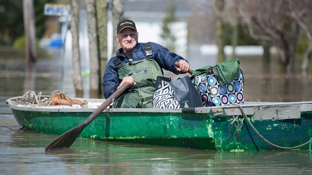 A man rows a small boat loaded with belongings down a street in the town of Rigaud, west of Montreal, Saturday, May 6, 2017, following flooding in the region. THE CANADIAN PRESS/Graham Hughes