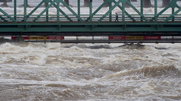 A pedestrian walks across the Chaudiere bridge as high waters on the Ottawa river pass just under Saturday May 6, 2017 in Ottawa. Parts of the region are seeing flood due to high water levels and heavy rains.THE CANADIAN PRESS/Adrian Wyld