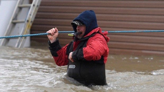 A resident holds his phone in his teeth as he navigates deep waters on Voisine Road in Rockland, Ont., about 40 kilometres east of Ottawa, as rising levels on the Ottawa River and heavy rains continue to cause flooding, on Sunday, May 7, 2017. THE CANADIAN PRESS/Justin Tang