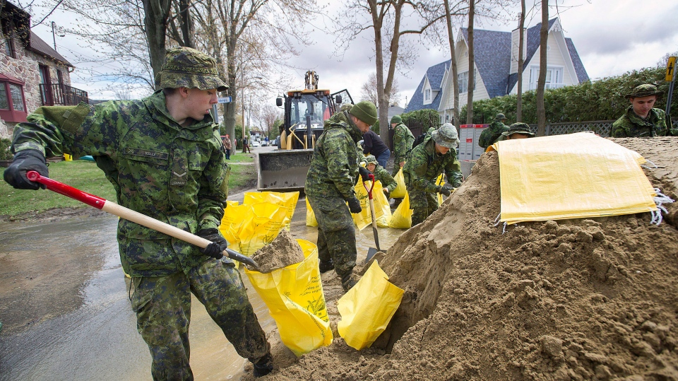 Members of the Canadian army fill sandbags in the Montreal borough of Pierrefonds, Sunday, May 7, 2017, following flooding in the region. THE CANADIAN PRESS/Graham Hughes