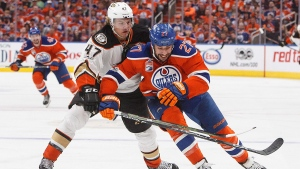Anaheim Ducks' Hampus Lindholm (47) and Edmonton Oilers' Milan Lucic (27) battle for the puck during the second period in game six of a second-round NHL hockey Stanley Cup playoff series in Edmonton on Sunday, May 7, 2017. (THE CANADIAN PRESS/Jason Franson)