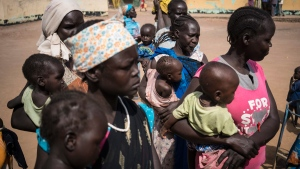 Mothers hold their children as they wait to have them screened for malnutrition at a UNICEF-supported Outpatient Therapeutic Program in Aweil, South Sudan, on March 13, 2017. (Mackenzie Knowles-Coursin/UNICEF via AP)