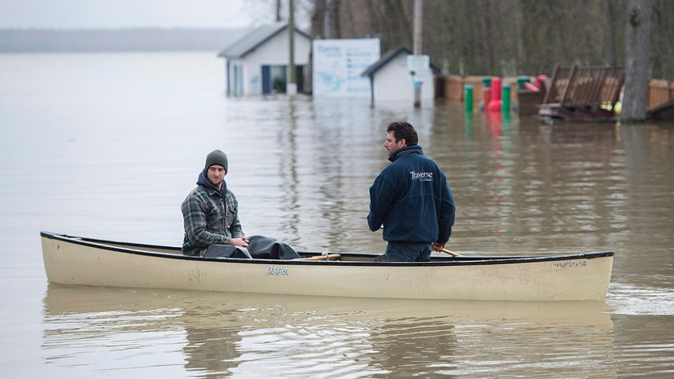 Two men use a canoe to move along the Hudson-Oka ferry loading ramp in the town of Hudson, Que., west of Montreal, Monday, May 8, 2017. (THE CANADIAN PRESS/Graham Hughes)