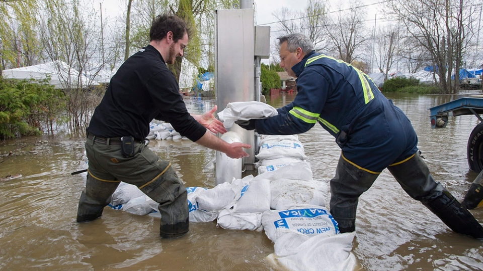 Volunteers place sandbags around an electrical panel in the town of Hudson, Que., west of Montreal, Monday, May 8, 2017. (THE CANADIAN PRESS/Graham Hughes)