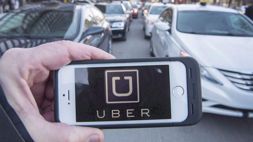 The Uber logo is seen in front of protesting taxi drivers at the Montreal courthouse, on February 2, 2016. (Ryan Remiorz/The Canadian Press)