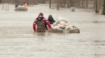 Residents are seen in waist high water transporting sandbags in a boat down a flooded street.