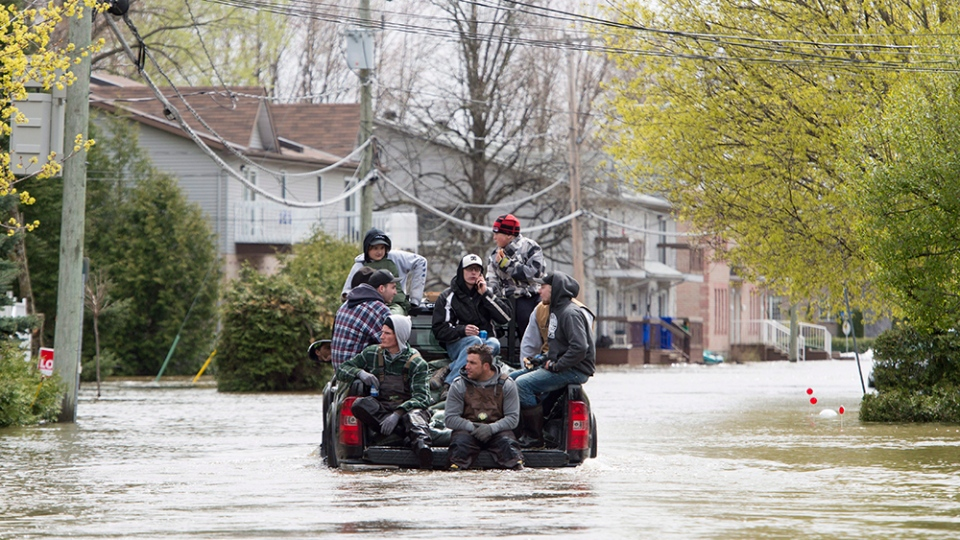 Volunteers ride in the back of a pick-up truck as they make their way into the flood zone Monday, May 8, 2017 in Gatineau, Que. (THE CANADIAN PRESS/Adrian Wyld)