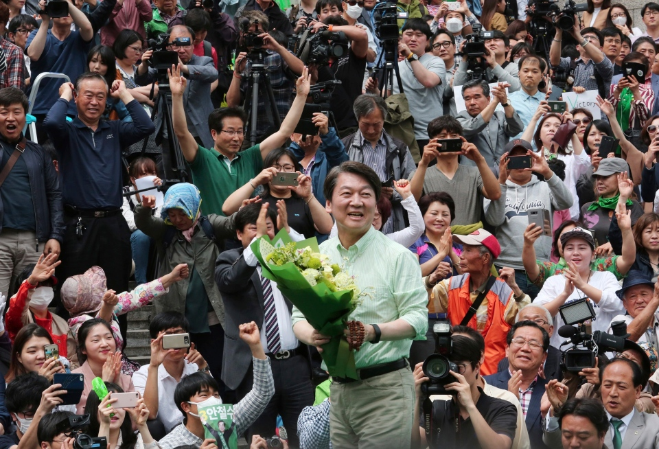 South Korean presidential candidate Ahn Cheol-soo of the People's Party holds flowers in front of supporters during an election campaign in Seoul, South Korea, Monday, May 8, 2017. (AP / Ahn Young-joon)