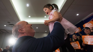 NDP Leader John Horgan picks up a toddler while campaigning in the battleground riding of Surrey-Guildford on the last day before the B.C. election. May 8, 2017. (THE CANADIAN PRESS/Darryl Dyck)