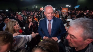 NDP Leader John Horgan is rushed backstage away from reporters after addressing supporters in Vancouver, B.C., in the early morning hours of Wednesday May 10, 2017. THE CANADIAN PRESS/Darryl Dyck