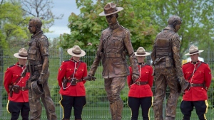 A bronze monument featuring life-size statues of Constables Doug Larche, Dave Ross and Fabrice Gevaudan, who were gunned down two years ago, is unveiled in Moncton, N.B., on June 4, 2016. (Andrew Vaughan/The Canadian Press)