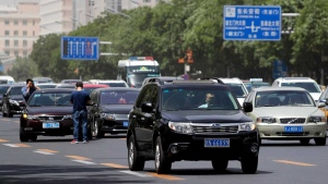 An SUV is driven past a traffic accident as motorists clogged with heavy traffic on a road in Beijing, Thursday, May 11, 2017. China's auto sales shrank in April as demand for most types of vehicles wilted, an industry group said Thursday. (AP Photo/Andy Wong)