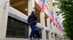 A member of the news media walks in front of the FBI headquarters building early in the morning in Washington, Wednesday, May 10, 2017. (AP Photo/J. David Ake)