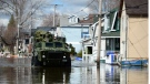 A military vehicle drives along a flooded street as waters breach the Gatineau River and flood the neighbourhood in Gatineau, Quebec on Wednesday, May 10, 2017. THE CANADIAN PRESS/Sean Kilpatrick