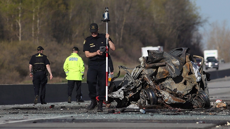 OPP officers attend the site of a crash in the westbound 401, northeast of Kingston, Ont. early Thursday, May 11, 2017. (THE CANADIAN PRESS/Lars Hagberg)