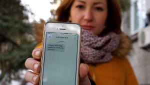 "In this photo taken Wednesday, Feb. 22, 2017, television journalist Julia Kirienko holds up her smartphone to show a text message reading, ""Ukrainian soldiers, they'll find your bodies when the snow melts'"" in Kiev, Ukraine. (Raphael Satter/AP Photo)"