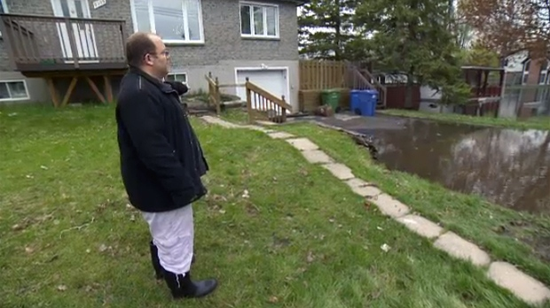 Itsik Romano stands in the front yard of his flood-damaged home on Macon St., Pierrefonds (May 11, 2017)
