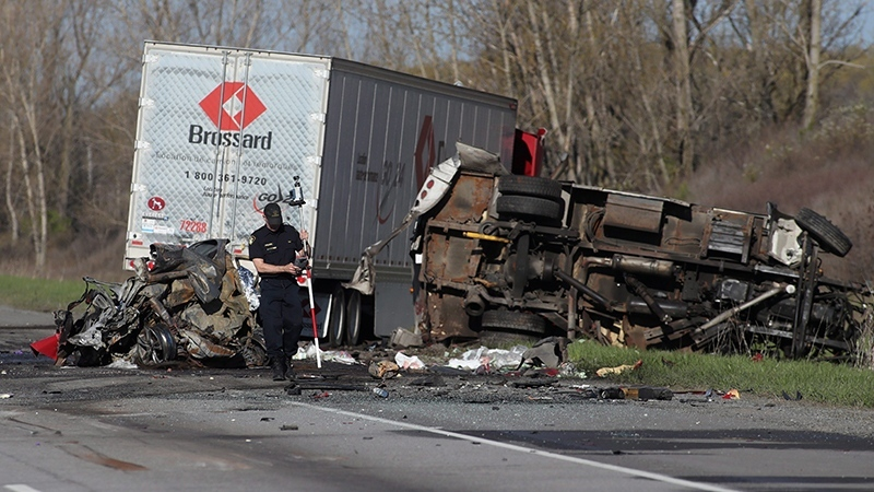 An OPP officer attends the site of a crash in the westbound 401, northeast of Kingston, Ont. early Thursday May 11, 2017. (THE CANADIAN PRESS/Lars Hagberg)