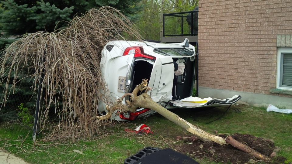A single-vehicle crash on Idle Creek Drive in Kitchener left the vehicle wedged between a tree and a house. (Scott Clarke / CTV Kitchener)
